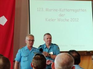 Zwei Marineangehörige vor Leinwand, eine Rede haltend